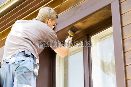 man with paintbrush painting wooden house