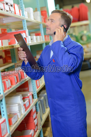 man in stores holding clipboard on