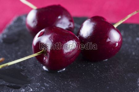 three cherries over black stone