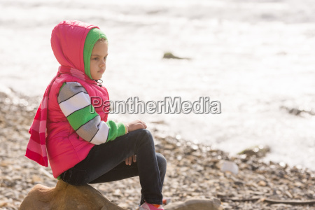 thoughtful girl sitting on a rock