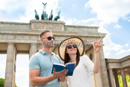 young couple reading tourist guide