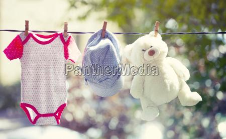baby kleidung hut und teddy haengen