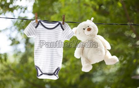 babykleidung und teddybaer haengen an der