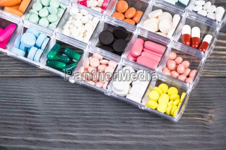 pillen im plastikbehaelter auf grauen tisch