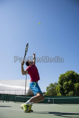tennis player serving a tennis ball