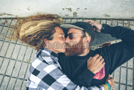 couple lying on skateboard kissing