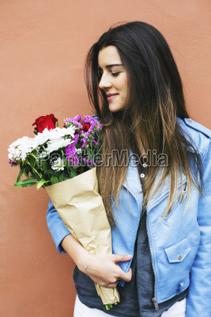 smiling young woman holding bunch of