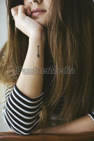 junge frau mit pfeil tatoo auf