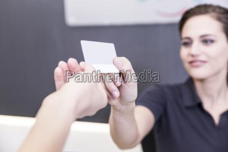 patient gibt versicherungskarte fuer die rezeptionistin