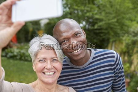 portrait of smiling couple taking selfie