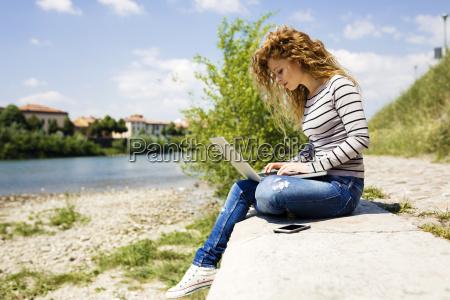 woman using laptop at riverside
