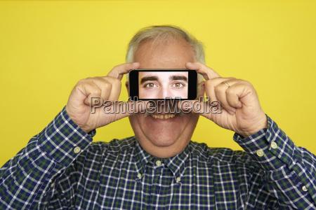 portrait of smiling senior man holding