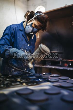 arbeiterin malt keramik mit spritzpistole