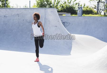 junge frau streckt sich im skatepark