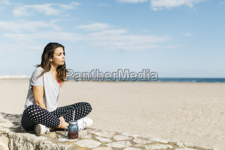 young woman with healthy drink sitting