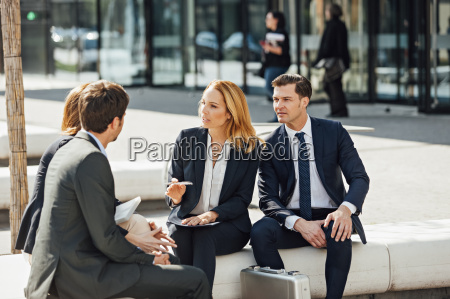business colleagues talking outside office building