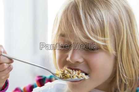 portrait of little girl eating granola