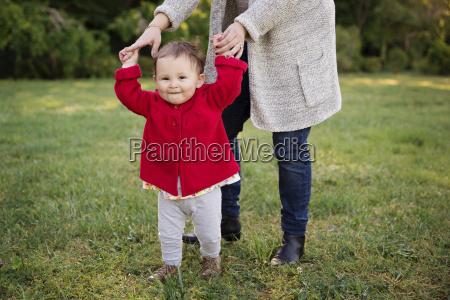 laechelndes kleinkind haelt die haende ihrer