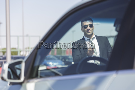 businessman at car park opening car