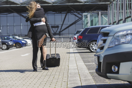 businessman with luggage at car park