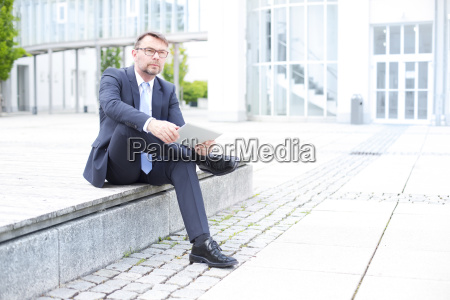 businessman sitting outdoors with digital tablet