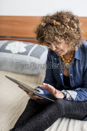 woman sitting on bed holding digital