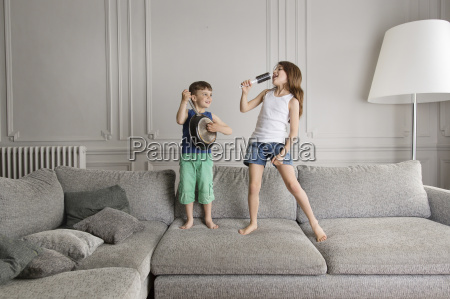 two little children playing with pan