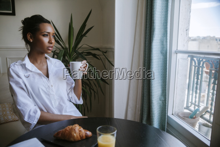 young woman sitting at breakfast with