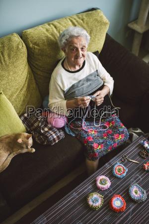 portrait of crocheting senior woman sitting