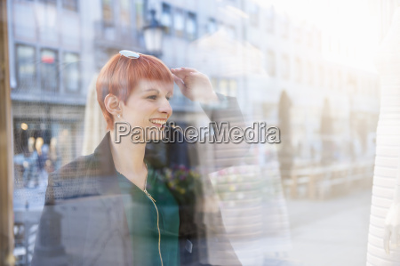 smiling young woman looking at shop