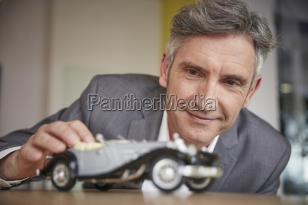 mature man playing with classic car