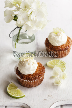 two lime cup cakes with cream