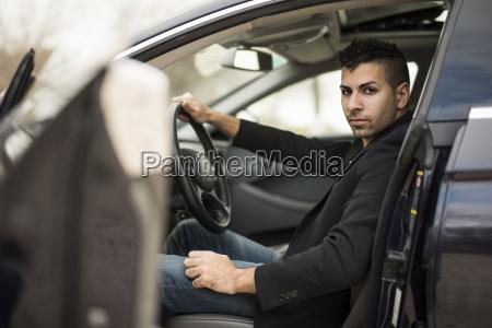 ernster junger mann sitzt im auto