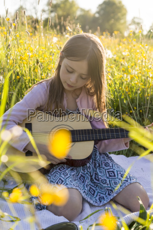 portrait of little girl playing guitar