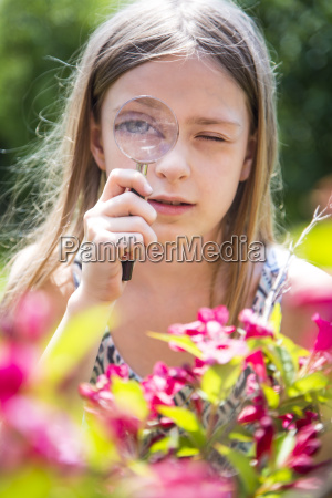 portrait of girl looking through magnifying