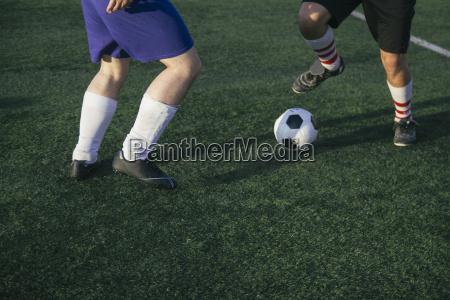 legs of football players on football