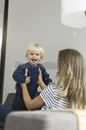 mother holding happy son at home