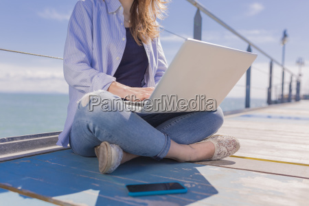 young woman with laptop and smartphone