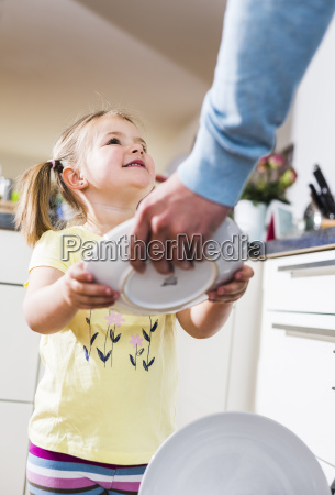 daughter helping father clearing dishwasher