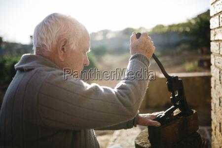 seniorenmensch der ein altes werkzeug zum