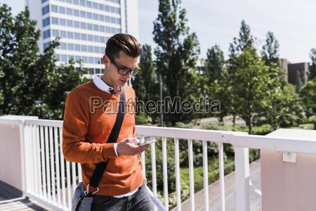 young man on bridge looking at