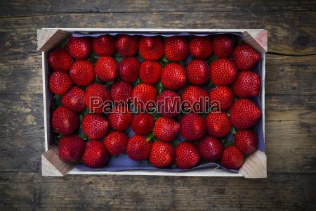 holzkiste mit sortierten erdbeeren