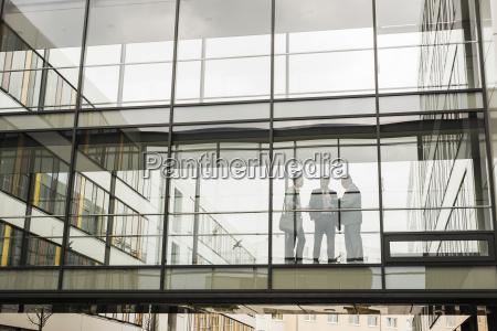 drei geschaeftsleute hinter glasfassade
