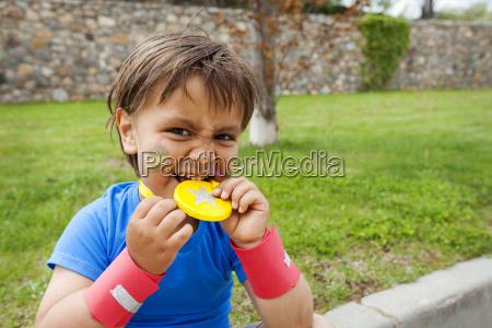kleiner junge beisst auf medaille