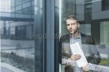 young businessman looking out of window