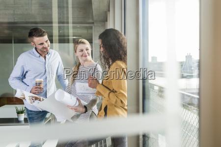 drei kollegen diskutieren plan im buero