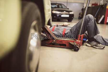 car mechanic on creeper dolly at