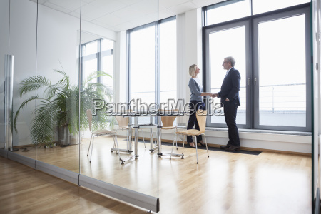businessman and woman in office shaking