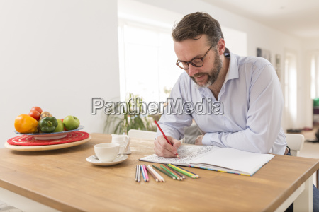 man with colouring book and coloured