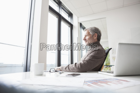 mature man sitting relaxed in office